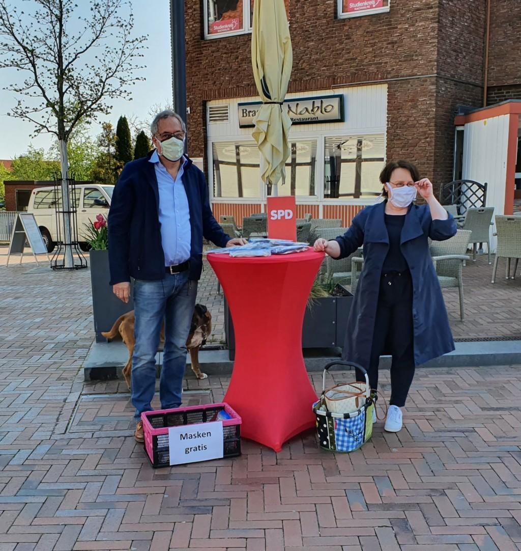 Landtagsabgeordnete Claudia Schüßler und Ortsvereinsvorsitzender Reinhard Dobelmann verteilen Schutzmasken am Thie